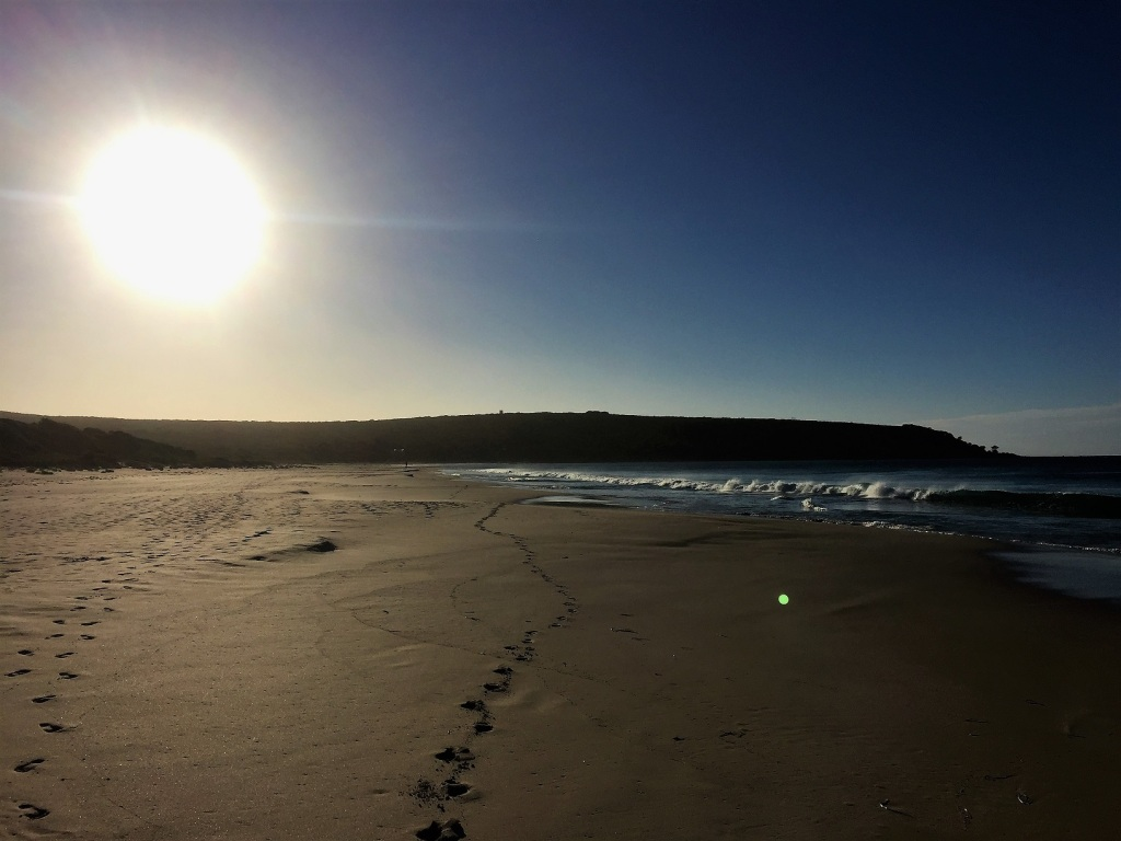 The sun low in the sky over the beach at Bunker Bay