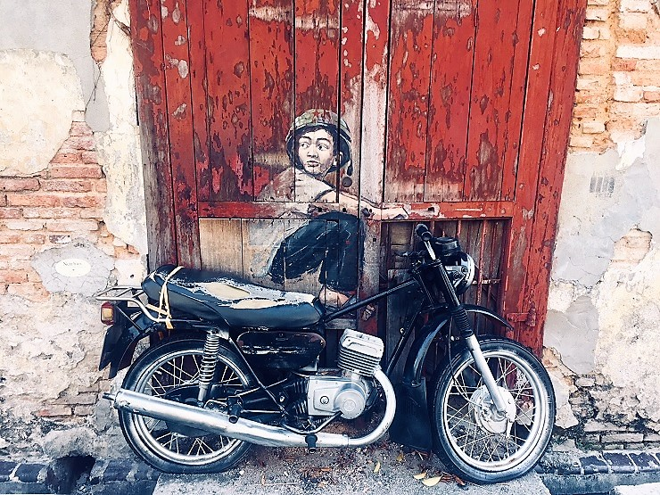 motorbike against a wall with painting of a boy sitting on it