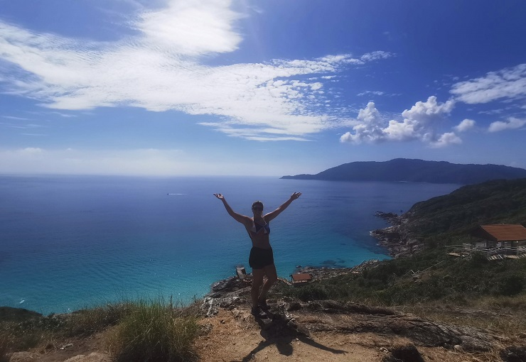 girl posing in front of turquoise sea and green hills