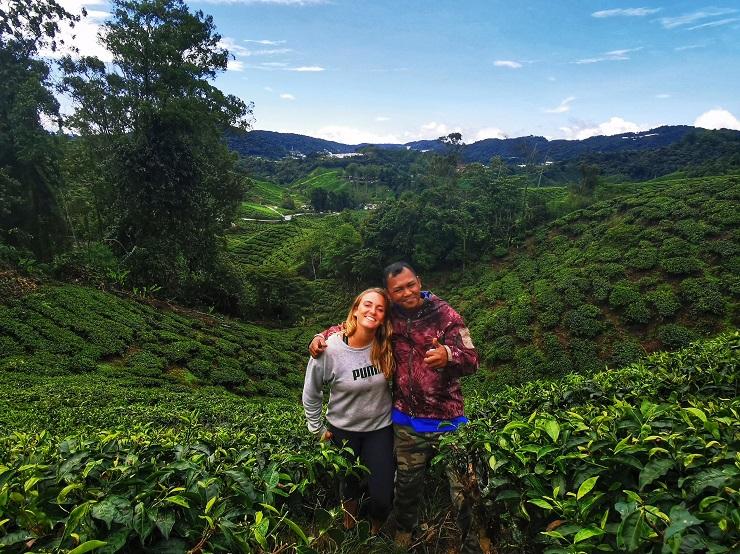 women and man standing amongst green tea plantation