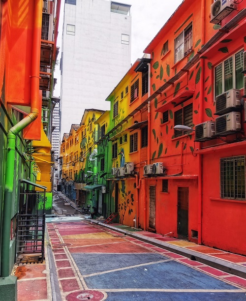 buildings painted orange, pink and yellow, decorated with street art