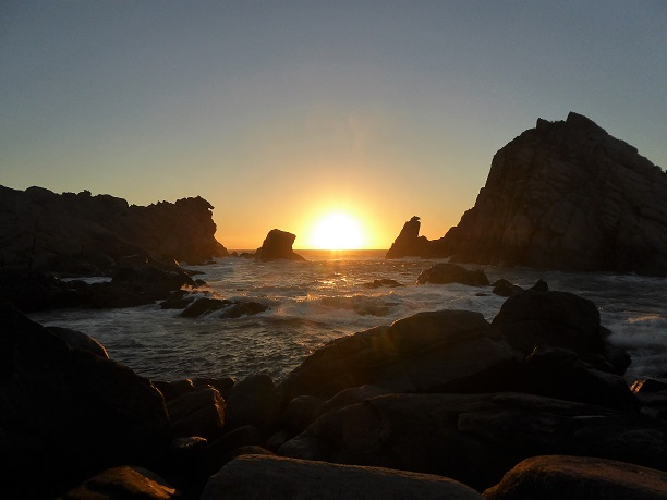 sun setting over the sea and between big rocks