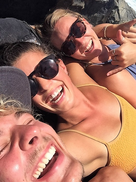 Three people grinning and laughing for a selfie