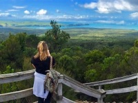 girl takingphoto across green forest and blue seas