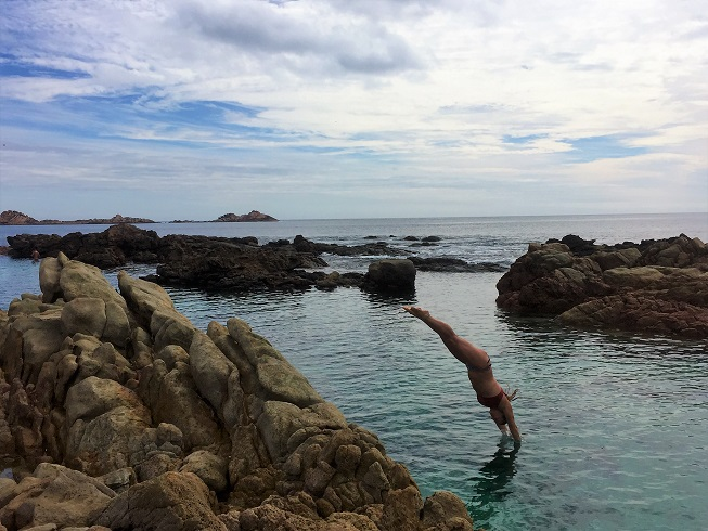 woman diving off rocks into the aquarium in the ocean
