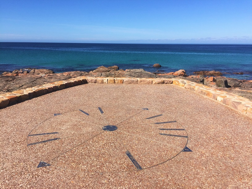 sun dial on the ground with ocean in the background